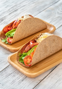 Tacos with ham and vegetables on the serving wooden plate
