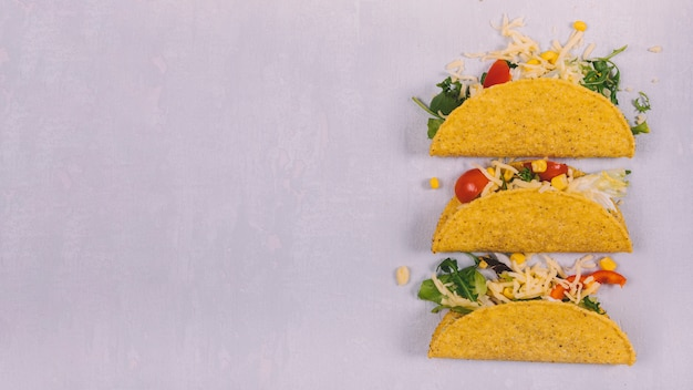 Tacos with meat and vegetables arranged on concrete background
