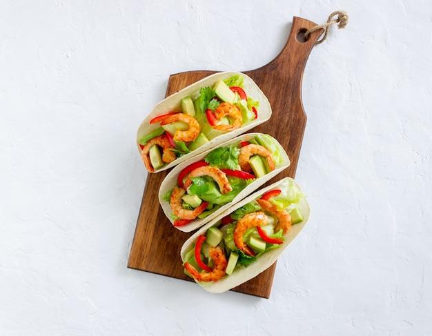 새우, 아보카도, 샐러드를 곁들인 타코. 멕시코 음식.