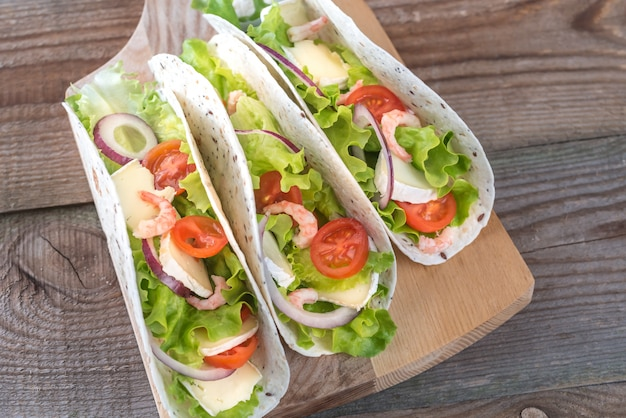 Tacos with shrimps, brie and fresh vegetables