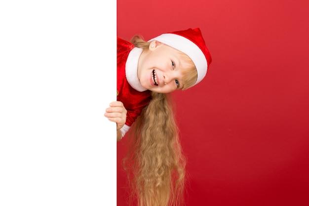 Тадаа. портрет милой маленькой девочки в рождественской шапке, смеющейся, глядя из-за пустого плаката с copyspace