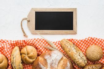 Tag-shaped chalkboard near bread and cloth