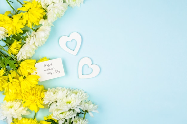 Tag with happy mothers day words near hearts and bunches of fresh flowers