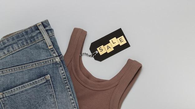 Тег со словом продажи из золотых букв и одежды на сером фоне