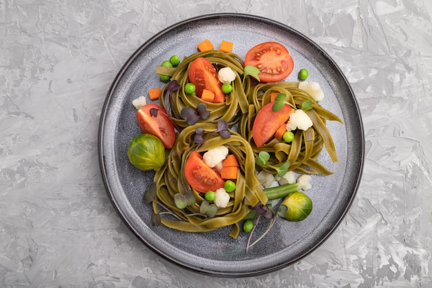 灰色のコンクリート表面にトマト、エンドウ豆、マイクログリーンの芽が付いたタリアテッレグリーンほうれん草パスタ