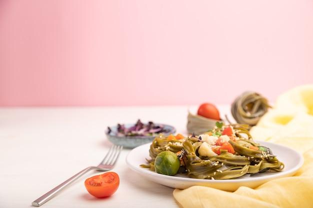 Тальятелле паста из зеленого шпината с ростками помидоров, гороха и микрозелени на бело-розовой поверхности и желтой ткани