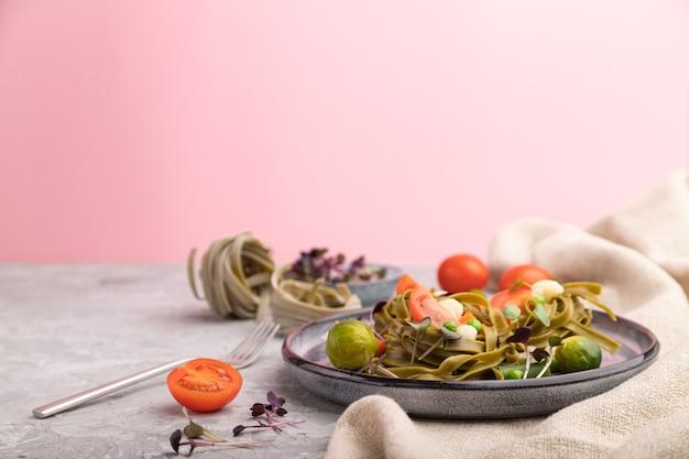 トマト、エンドウ豆、マイクログリーンスプラウトのタリアテッレグリーンほうれん草パスタ。側面図、コピースペース。