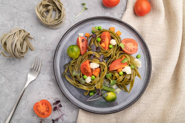 Tagliatelle green spinach pasta with tomato, pea and microgreen sprouts on a gray concrete surface and linen textile