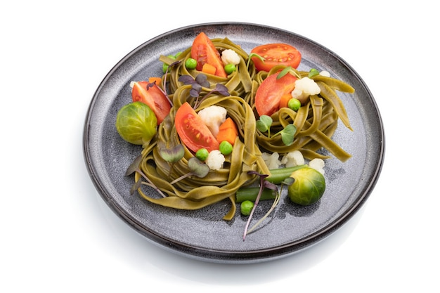 Tagliatelle green spinach pasta with tomato, pea and microgreen sprouts isolated on white surface