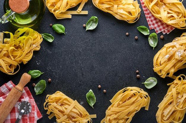 탈리아텔레. 집에서 만든 파스타, 바질 잎, 밀가루, 후추, 올리브 오일, 체리 토마토를 어두운 검정색 배경에. 음식 개념입니다. 조롱. 복사 공간이 있는 가로.