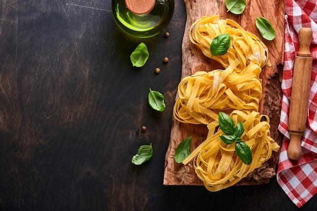 Тальятелле. домашняя паста, листья базилика, мука, перец, оливковое масло, помидоры черри и скалка и нож для макарон на темном старом деревянном фоне. концепция питания. макет. горизонтально с копией пространства.