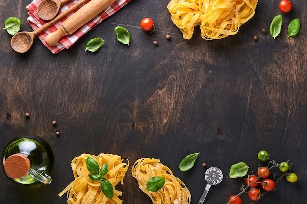 탈리아텔레. 집에서 만든 파스타, 바질 잎, 밀가루, 후추, 올리브 오일, 체리 토마토, 롤링 핀, 파스타 칼이 어두운 오래된 나무 배경에 있습니다. 음식 개념입니다. 조롱. 복사 공간이 있는 가로.