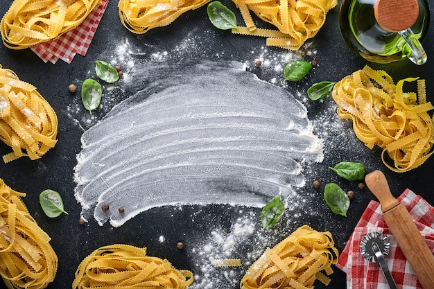Tagliatelle. homemade pasta, basil leaves, flour, pepper, olive oil and cherry tomato on dark black background. food concept. mock up. horizontal with copy space.