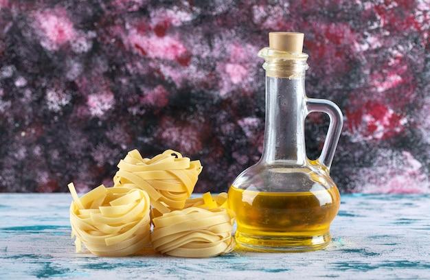 Nidi di tagliatelle e bicchiere di olio d'oliva.