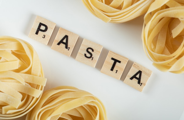 Tagliatelle nests on white surface with wooden letters.