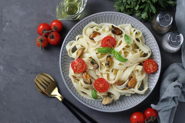 Паста тальятелле с мидиями и помидорами черри на серой тарелке