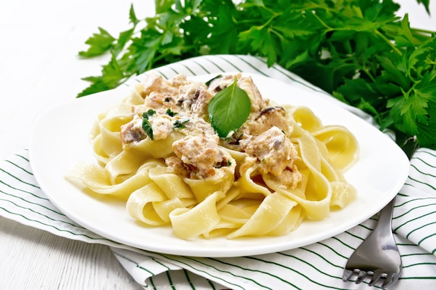Tagliatelle pasta with salmon, cream, garlic and herbs in a plate on a kitchen towel, fork, parsley and basil on light wooden board background