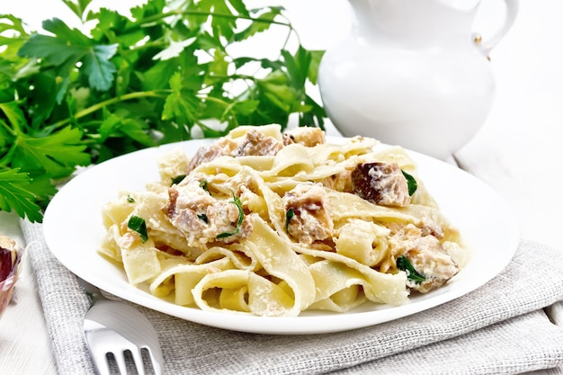 Tagliatelle pasta with salmon, cream, garlic and herbs in a plate on a napkin, fork, parsley and basil on the background of light wooden board