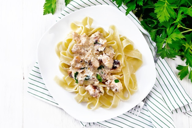 Tagliatelle pasta with salmon, cream, garlic and herbs in a plate on a towel, fork, parsley and basil on the background of light wooden board from above