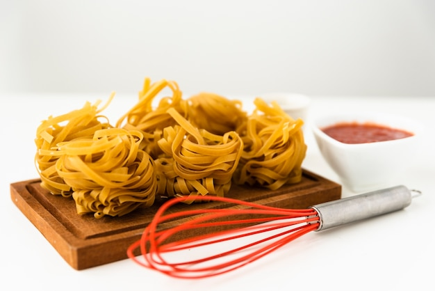 Tagliatelle pasta on wooden cutting board with red whisk over white background
