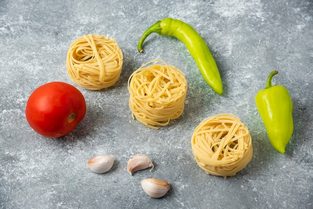 タリアテッレの生パスタの巣と野菜を大理石のテーブルに。