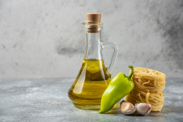 Tagliatelle raw pasta nests, bottle of oil and vegetables on marble background.