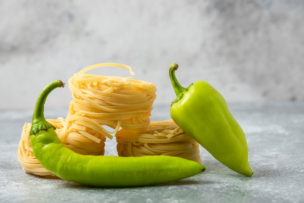 Tagliatelle raw pasta nests and green peppers on marble table.