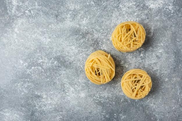 Tagliatelle di pasta cruda nidi isolati su sfondo marmo.