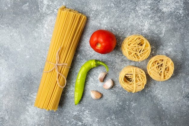 Tagliatelle raw pasta nests, spaghetti and vegetables on marble surface.