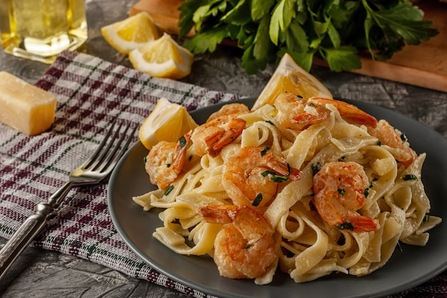 Tagliatelle with prawns and parsley on a gray table