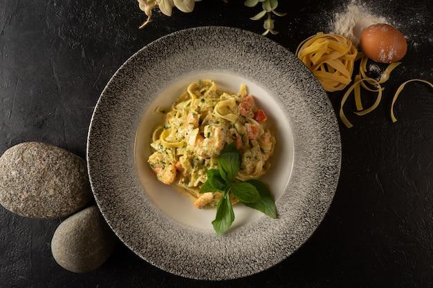 Тальятелле с овощами из креветок и базиликом. горячее блюдо из макарон и морепродуктов на темном фоне