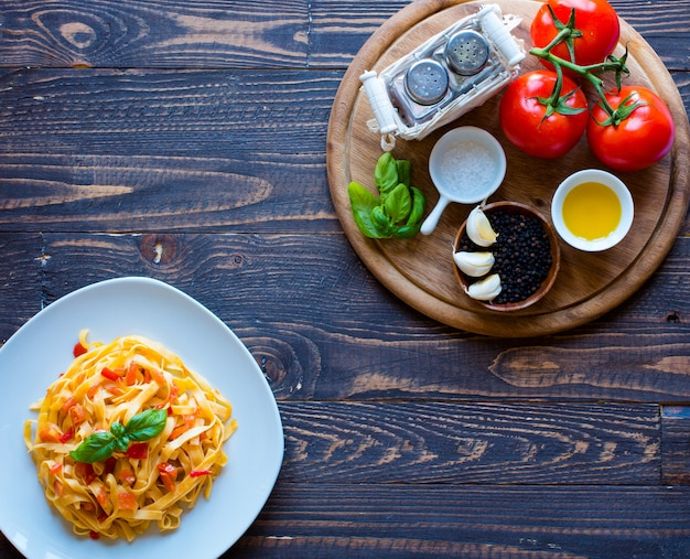 Tagliatelle with tomato and basil made at home on a wooden background.