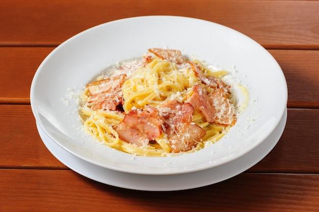 Tagliatelli carbanara italian cuisine on plate rustic kitchen table background