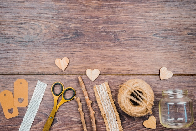 Tags; ruler; scissor; sticks; lace ribbon; empty jar and heart shape on wooden backdrop