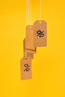 Бирки с нарисованными процентами висят на ниточках на желтом фоне, концепция скидок и распродаж