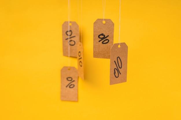 그려진 비율이있는 태그는 노란색 배경, 할인 및 판매 개념에 문자열에 매달려 있습니다.