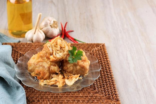 Tahu isi hot jeletot или индонезийский жареный тофу, традиционная закуска из хрустящего тофу, фаршированная овощами stir fry, подается с чили или соусом чили. копировать пространство для текста