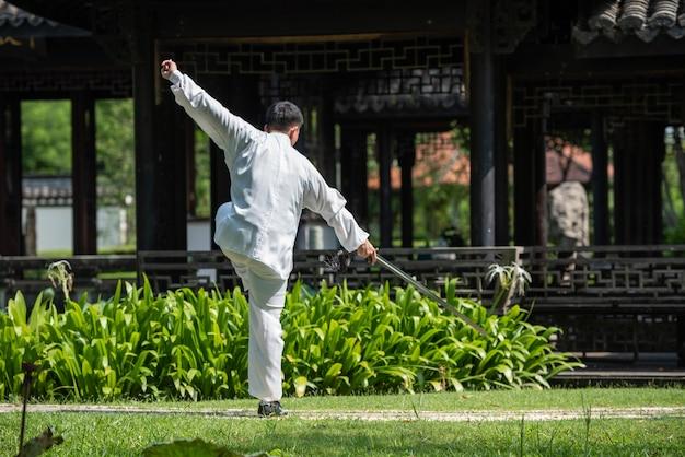 Азиатский человек разрабатывая с шпагой хиа tai в утре на парке, китайских боевых искусствах, здоровой концепции заботы на всю жизнь.