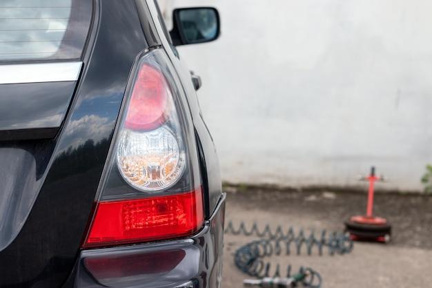Задний фонарь черного автомобиля в сервисном центре шин. выборочный фокус. крупным планом вид