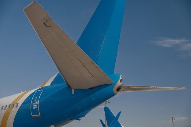 背景に青い空がある空港の航空機の尾翼。飛行機、輸送の概念