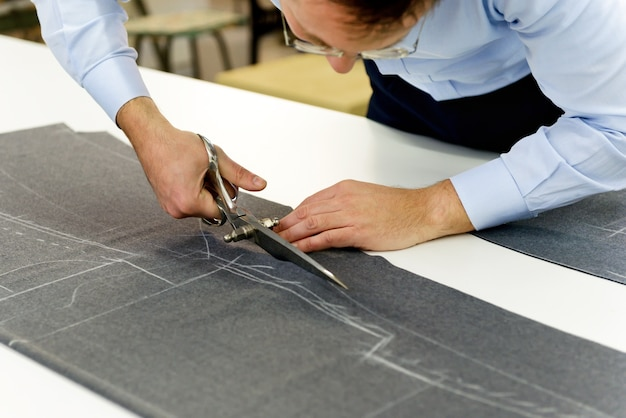 Tailor carefully cutting grey fabric in a workshop using large shears to follow the chalked pattern on the textile