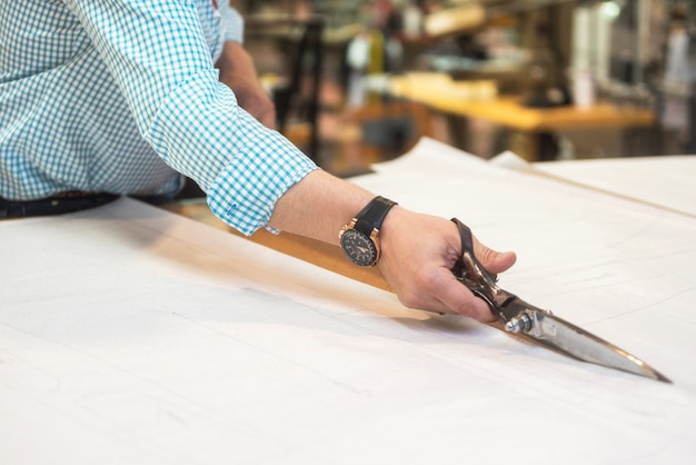 Tailor cutting out the marked pattern on fabric with large scissors on the workbench in his shop