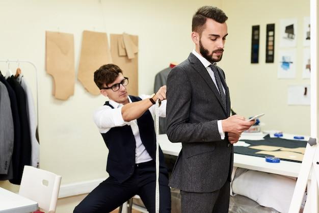 Tailor fitting handsome businessman for bespoke suit