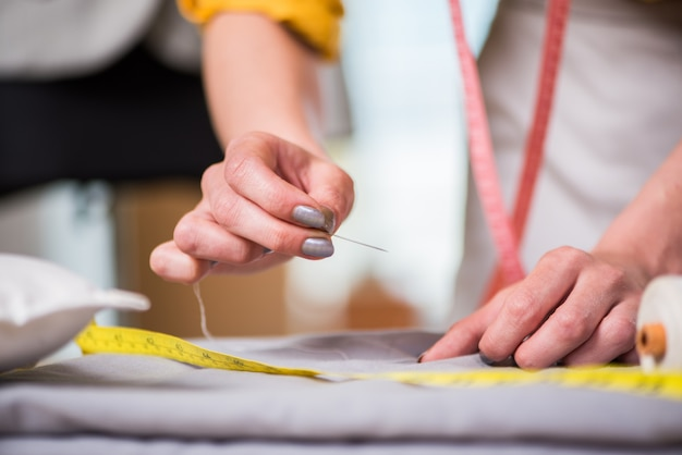 Tailor hands working on new clothing
