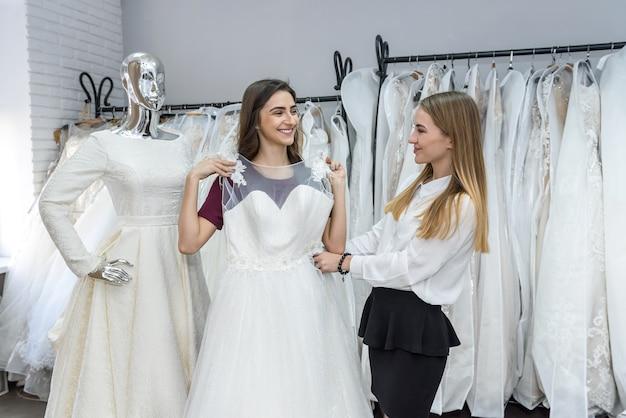 花嫁がドレスを試着するのを助けるウェディング サロンの仕立て屋