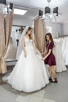花嫁がドレスを試着するのを助ける結婚式のサロンで仕立て