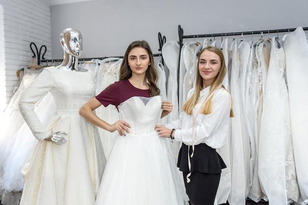 Портной в свадебном салоне помогает невесте примерить платье