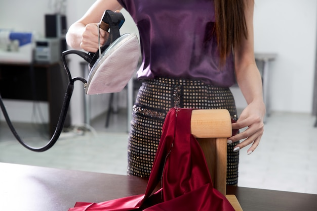 生地をアイロンで仕立てます。裁縫ワークショップ、モダンなアトリエスタジオで仕立て屋の鉄の服