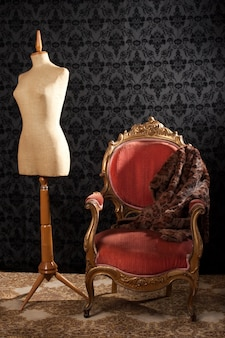 Tailor mannequin and armchair on a vintage wall