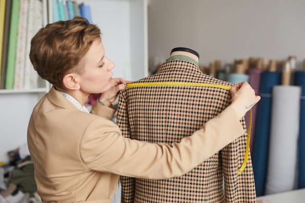 Tailor measuring shoulder length on the jacket with tape measure before show it to the client